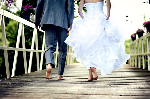 Loveandfriends newly wed couple in wedding dress runnign barefoot together